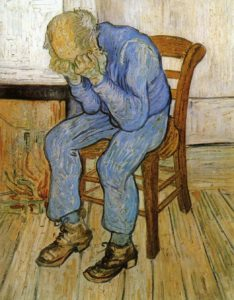 A bald old man, dressed all in blue, sits with hands buried in face upon a wooden chair.