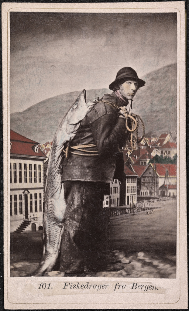 A young man in a faded old hand-colored photo. He's got a thick oily square-cut coat and slacks (some kind of old-fashioned waterproofing?) and a wide-brimmed hat. A giant fish as long as he is tall is slung over his shoulder.