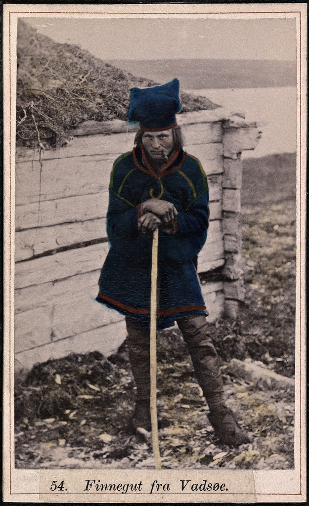a 1900s Norwegian fisherman in a sturdy square deep blue sweater/coat/dress and a strange puffy-topped hat (looks kind of like a chef's hat), also colored with the same striking blue. Resting on a staff with a pipe in his mouth, head bent slightly down but eyes beaming up and out.