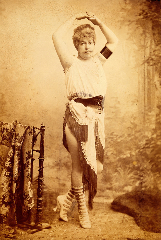 A sepia picture of a man with curly hair and a mustache, hands meet overhead, a long skirt comprised of a linen cloth with long tassels worn lopsided so one thigh is mostly revealed and on the other side, the shins are covered. Long tassels on the skirt. A slightly puffy soft tank top. A girdle holds everything in place. shin-covering boots with high square heels and like 20 bands-with-a-buckle per boot (with a little skin showing between each band).
