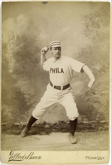 An early-1900s baseball player from team Philly winds back to throw. Stern eyes and a broad and full but not-quite handlebar mustache.