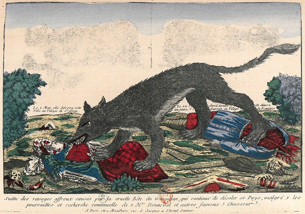 A sepia-touched picture of a shaggy dark-gray wolf devouring a woman in a green dress. Her arm is already reduced to bone. Its hind pays are on the red squished rib cage of a headless and limbless fellow in a long blue coat-frock; the guys limbs, head and black wide-brim hat lay nearby. Ground is yellow with splashes of green bush and grass. Writing underneath is french, talking about how the cruel beast of Genudan continues to carry out horrifying attacks even as the effort of M. Denneval and other famous hunters continue.
